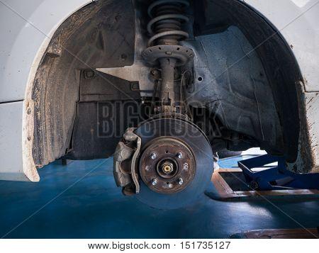 Front wheel disk brake and caliper maintenance job in progress.