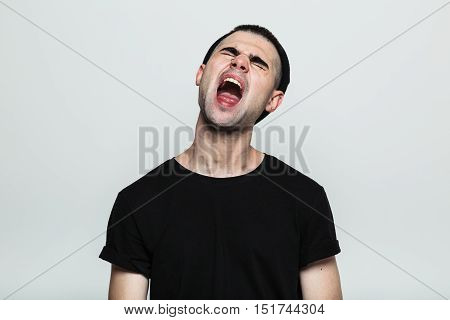 Studio shot of an annoyed man screaming, his head tilted back