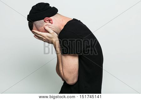 Unrecognizable man hiding and closed face with hands in studio on white background. Side view.