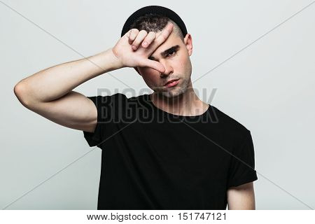 Close up portrait of young handsome guy in black T-shirt and hat showing loser gesture on his forehead. Copyspace.