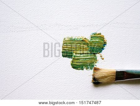 White canvas and oil brush stroke. Green and yellow paint of natural palette. Oil brush stroke on canvas. Oil painting hobby. Painted canvas image with place for text. White background banner template