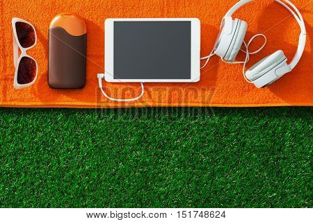 Sunglasses digital tablet suntan lotion and towel on the garden grass: summertime sunbathing and relax