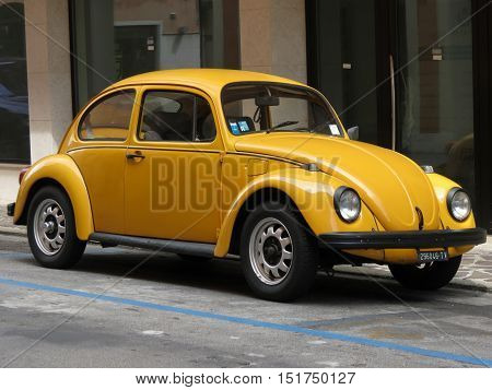 TREVISO ITALY - CIRCA JULY 2014: Yellow Volkswagen Beetle vintage car parked in a street of the city centre.