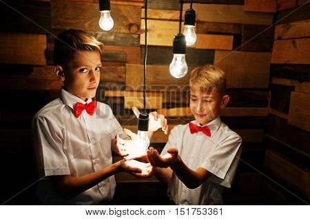 Two Brothers Posed At Studio Room Wooden Wall With Enabled Light Bulbs