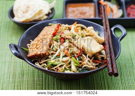 Mi goreng, mee goreng Indonesian cuisine, spicy stir fried noodles with tempeh and assortment of asian sauces