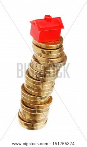 Red litle plastic house on top of an unstable stack of golden coins isolated on white