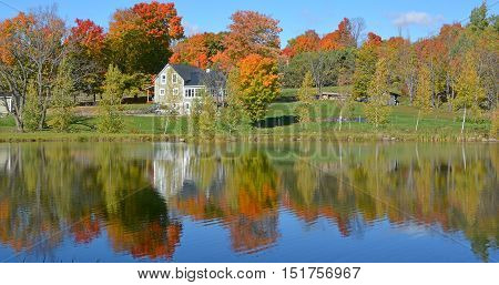 BROMONT QUEBEC CANADA 10 14 16: Typical canadian house reflect in a lake design has long needed to be adapted to Canada's climate and geography, and also reflected the uniqueness of Canadian culture.