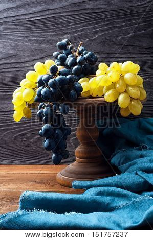 Still life with blue and green grapes on a background of black textured wood with copy space