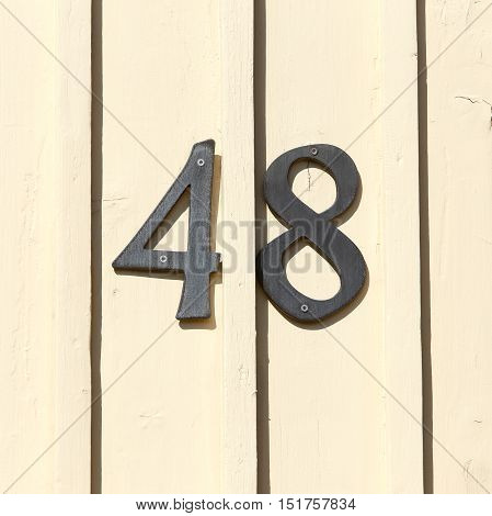 Street address number 48 on a light yellow wooden wall.