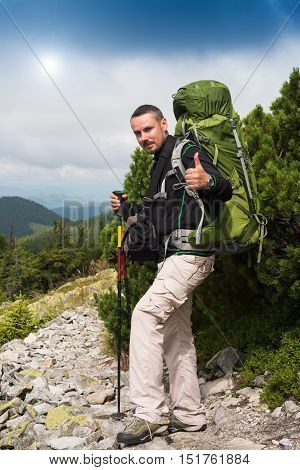 Happy hiker winning reaching life goal success freedom and happiness achievement in mountains. Thumbs-up. Sign OK. Hiker with backpack on top of a mountain.Concept of success