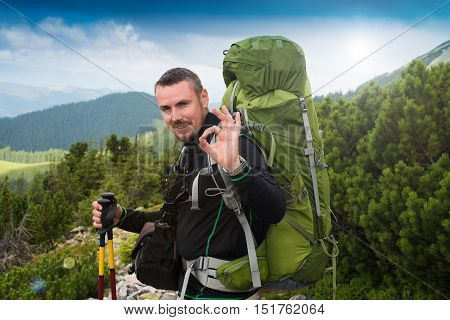 Happy hiker winning reaching life goal success freedom and happiness achievement in mountains. Sign OK. Hiker with backpack on top of a mountain.Concept of success