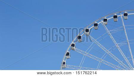 Part of a Ferris wheel on blue sky.