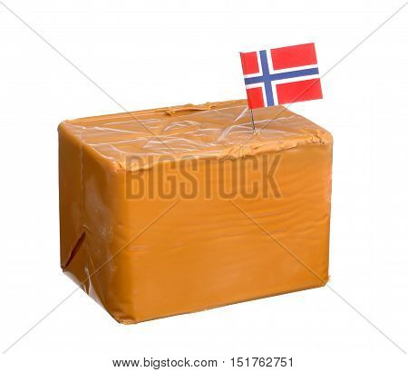 A block of Norwegian whey cheese made with cows cream and goats milk with a Norwegian flag isolated on white background.