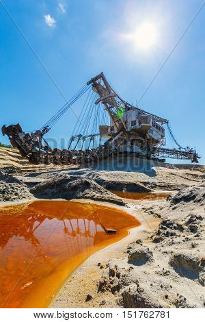 multi bucket excavator, giant stacker, absetzer in career. red water rich in minerals