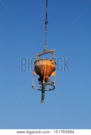 Closeup of hopper suspended from a highrise construction crane against a blue sky.