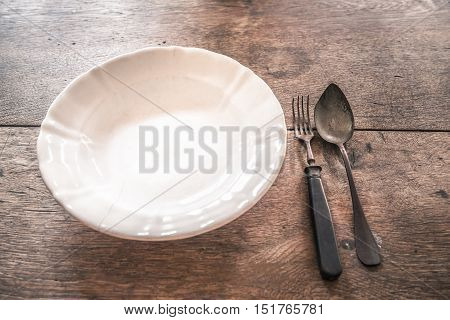 Rustic weathered tableware on wooden table - Retro image with an old fissured plate and rusty fork and spoon on a wooden table. Great as a frame or background with copy space.