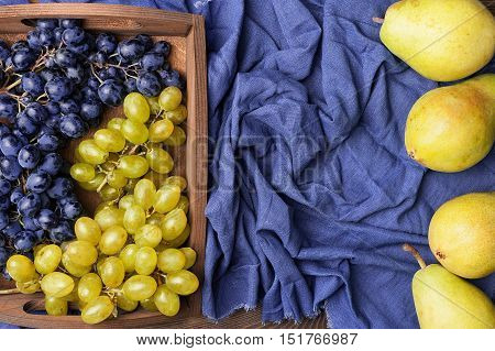 Still life with blue and green grapes and pears top view