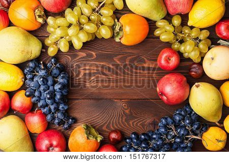 Frame autumn fruits on a wooden board top view with copy space