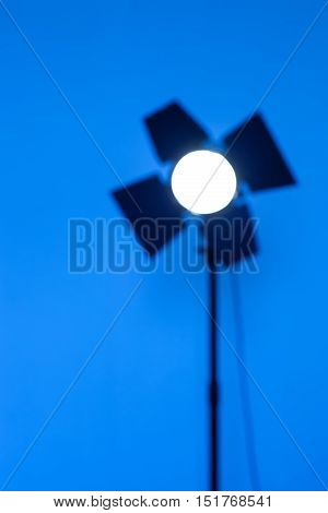 Photographic Equipment for photo shoots. Blurred outlines of lighting monoblock on blue background