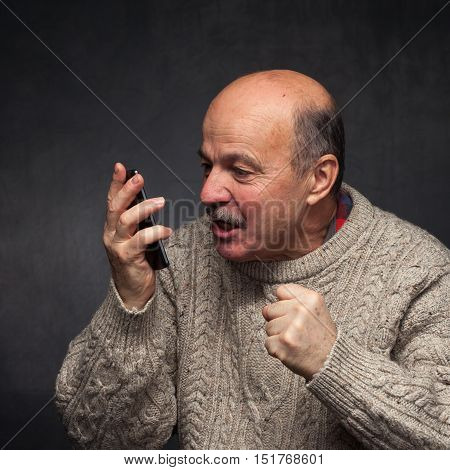 Older Man Yells Into The Phone In Anger.