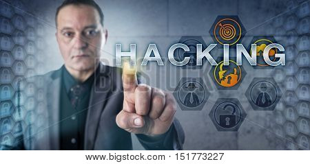 Mature male corporate security expert touching HACKING onscreen. Information technology metaphor for the activity of identifying network vulnerabilities and exploiting computer security weaknesses.