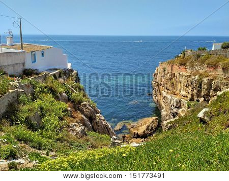 View to old houses on cliff near the ocean in Peniche, Portugal