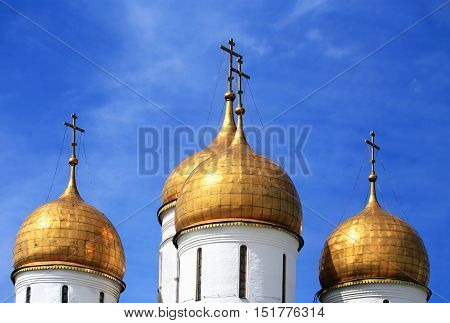 Golden onion domes of the fifteenth century orthodox temple in Moscow Kremlin