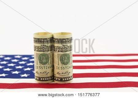 Still life of pair of dollars on American flag. Horizontal photo with copy space.