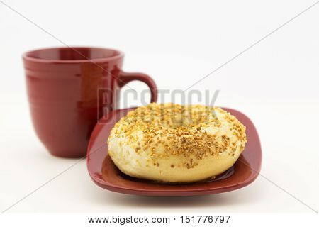 Fresh garlic bagel on square red plate with matching mug. Horizontal food image with copy space.