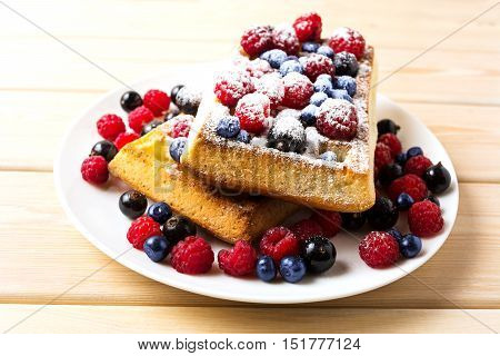 Belgian waffles with blueberry and raspberry powdered by caster sugar. Breakfast soft waffles with fresh berries.