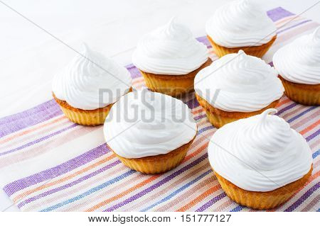 Cupcakes with white whipped cream swirl. Homemade cupcakes with whipped cream. Homemade cupcakes served for party.