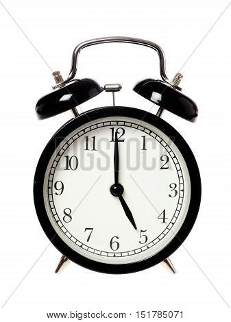 One black alarrm clock displays the time five o clock isolated on white background.