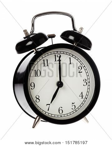 One black alaram clock dispaly time 7 o clock on an analog clock face isolated on white background.
