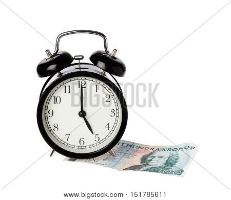 Alarm clock at five o clock on a Swedish one hundred krona banknote isolated on white background.