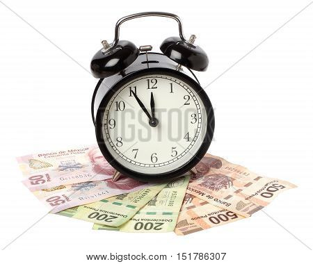 One black alaram clock on Mexican Pesos banknotes isolated on white.