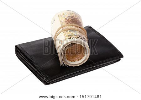 One roll Norwegian 500 Kroner banknotes on top a black wallet isolated onwhite background.