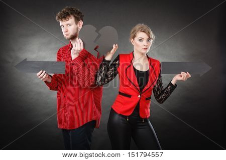 Relationship problem feelings depressing sadness breakup concept. Young pair showing heartbreak symbols. Man with woman holding arrows with broken heart pointing in opposite directions.