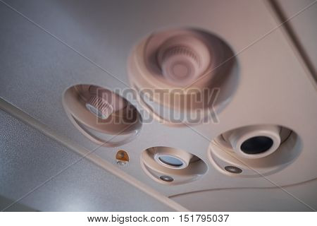 Closeup of overhead light and fan in plane