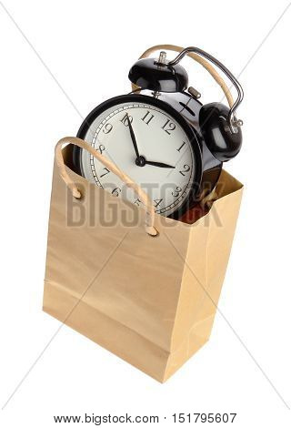 One black alarm clock inside a brown paper bagwith handles isolated on white.