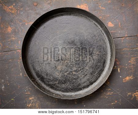 Old Cast Iron Frying Pan On The Black Wooden Table Close-Up Top View