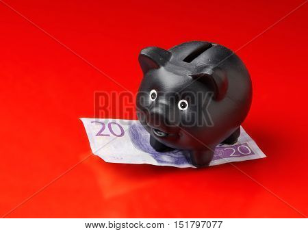 Black piggy bank on a Swedish twenty krona banknote isolated on red background.
