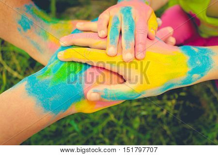 Four hands painted in different colors. Concept of love, friendship, happiness in family. Toned image.