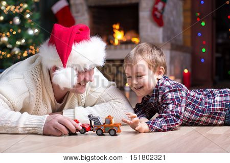 Adorable kid boy and father playing with cars toys at home. Happy child having fun with gifts. Colorful christmas lights on background. Family, holiday, kids lifestyle concept.