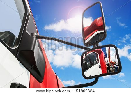 rear-view mirror on the truck. sky reflected in rearview mirror. focus on the bottom rear-view mirror