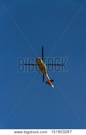 ROME – AUGUST 23: Firefighting helicopter carrying bucket containing water from Mediterranean Sea to put out fires on scrubland on August 23 2016 in Rome.