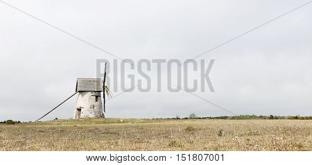 Windmill to the left in the picture of Gotland heathland on a cloudy day.