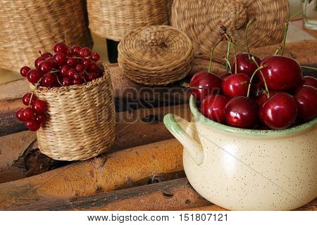 Sweet cherry in ceramic bowl and red currant in wattled bast basket