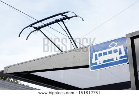 A tram stop with tram stop sign and the pantograph of an electric powered tram visible.