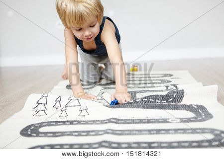 Indoor Shot Of Happy Cheerful Caucasian Two-year Old Boy With Blonde Hair Playing With His Toys, Cra