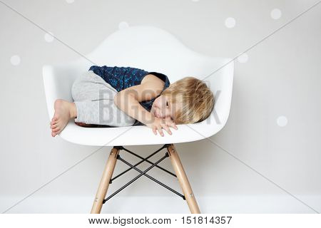 Happy Carefree Childhood. Sweet Caucasian Infant Rolling Himself Up In White Designer Chair, Hiding